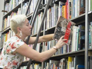 Graduate Intern Eden Collins reshelves books in the Artpace Archive & Resource Library